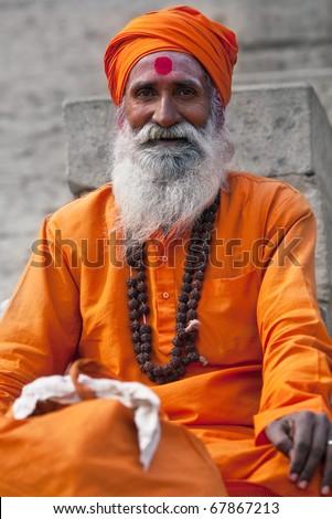 VARANASI - JANUARY 13: Shaiva sadhu (holy man) seeks alms in front of a temple on January 13, 2010 in Varanasi, State of Uttar Pradesh, India. - stock photo