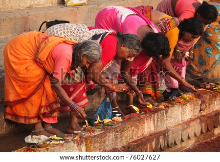 VARANASI - 6 NOVEMBER: Hindu people wash themselves in the river Ganga in the holy city of Varanasi.  The holy ritual of washing is held every day -Varanasi, India, November 6 2010 - stock photo