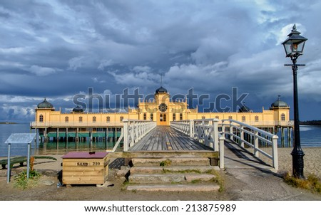 VARBERG, SWEDEN - JULY 2: Sun breaks through dark clouds to shine on the public bath on July 2, 2014 in Varberg. This iconic vintage bath dates back to 1903 and is one of the most famous in Sweden. - stock photo