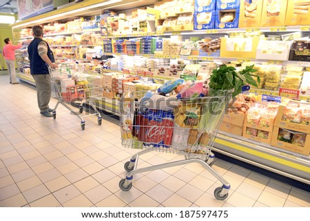 VARESE, ITALY-APRIL 11, 2014: Full shopping cart, and customers shopping in a supermarket, in Varese.