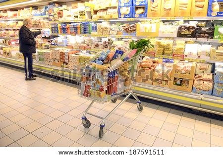VARESE, ITALY-APRIL 11, 2014: Full shopping cart in a supermarket aisle, in Varese.