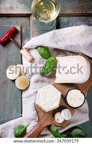 Variation of cheese, served with fresh basil, bread and glass of white wine over turquoise wooden table. Top view. See series - stock photo