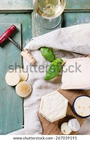 Variation of cheese, served with fresh basil, bread and glass of white wine over turquoise wooden table. See series - stock photo