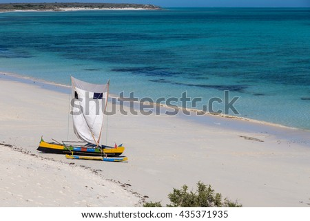 Varicolored bright boats with wight sail on the beach, Madagascar - stock photo