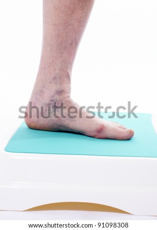 Varicose veins closeup, foot on modular bath step, image isolated on white background - stock photo