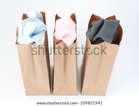 Varied colors of cloth in each of three brown paper bags - stock photo