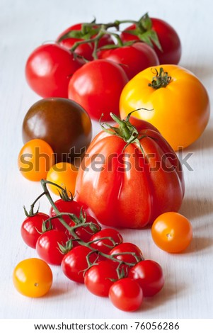 Varied types of tomatoes on a white garden table. - stock photo