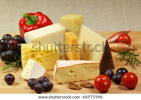 Varieties of hard cheese on a wooden board. Grapes, tomatoes, rosemary and nuts.