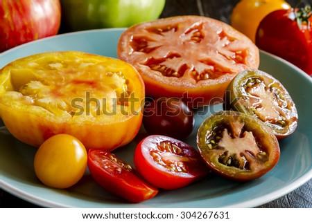 Varieties of sliced heirloom tomatoes sitting on light blue plate - stock photo