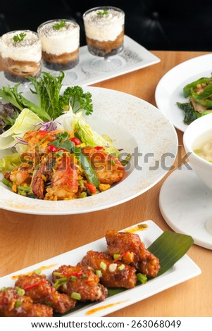 Varieties of Thai foods and appetizers covering a table. Shallow depth of field. - stock photo