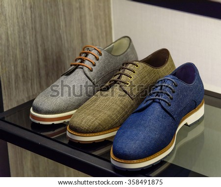 Variety colorful leather casual derby shoes on the shelf in the menâ??s fashion footwear and accessories shop in Singapore. Casual, fashion and work shoes for men. - stock photo