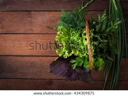 Variety fresh organic herbs (lettuce, arugula, dill, mint, red lettuce and onion) on wooden background in rustic style. Top view - stock photo