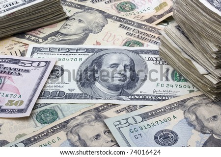 Variety of American money laid out under a stack of cash. - stock photo