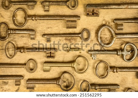 Variety of antique vintage keys on an old wooden background - stock photo