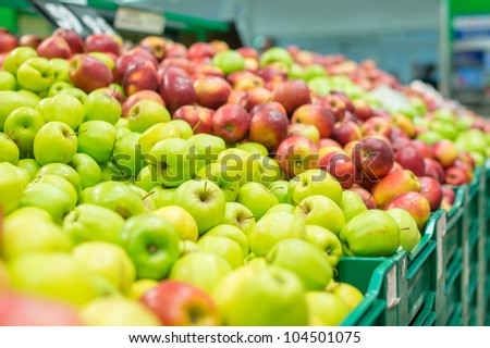 Variety of apples in boxes in supermarket - stock photo