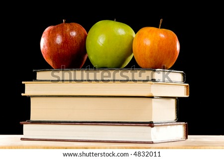 Variety of apples on top of a stack of school books