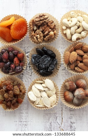 Variety of 9 assorted nuts and dried fruits - stock photo