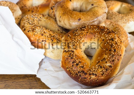 Variety of Authentic New York style bagels with seeds in a paper bag