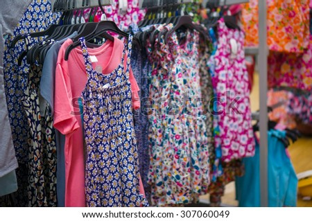 Variety of beautiful baby girl dresses on stands and hangers in supermarket - stock photo