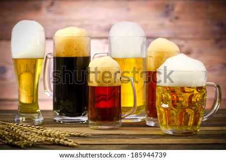 Variety of beer glasses on a wooden table - stock photo
