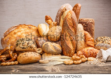 Variety of bread on old wooden table - stock photo
