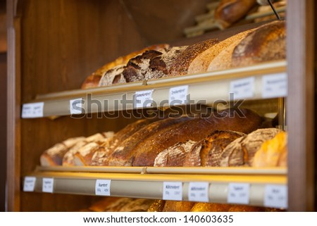 Variety of breads displayed in display cabinet in bakery - stock photo
