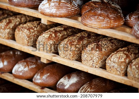 Variety of breads displayed on shelves in bakery - stock photo