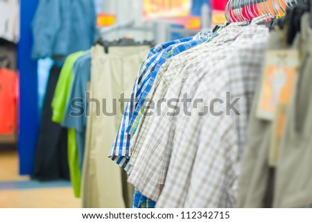 Variety of bright shirts and trousers on stands in supermarket