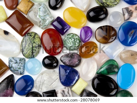 Variety of cabochon gemstones on white background