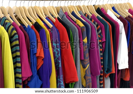 Variety of casual clothes of different colors on wooden hangers - stock photo
