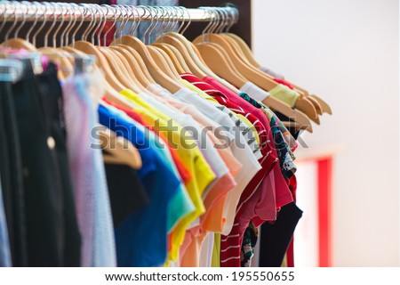 Variety of clothes hanging on rack in boutique - stock photo
