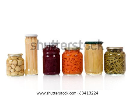 Variety of colorful canned vegetables in glass pot. Food, preserve concept. Studio shot. White background. Copy space.