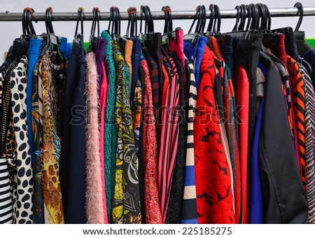 Variety of colorful fashion clothing on hanging-gray background - stock photo