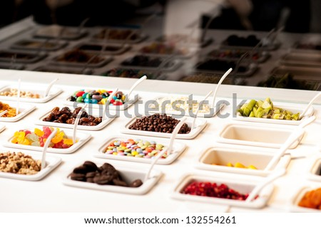 Variety of colorful toppings and yummy jellies displayed. - stock photo
