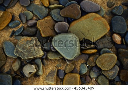 Variety of colorful wet pebbles at the beach. - stock photo