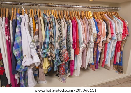 Variety of colorful womens clothing hanging on rail in fashion shop - stock photo