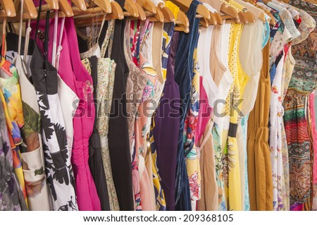 Variety of colorful womens summer clothing hanging on rail in fashion shop - stock photo