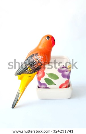 Variety of Colorfully Painted Ceramic Pots and bird sculptures on a white background - stock photo