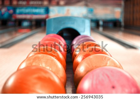 Variety of colors. Close up of bright red bowling ball lying in the rows of other colorful balls