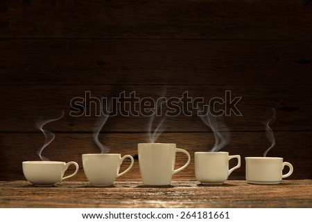 Variety of cups of coffee with smoke on wooden background,This photo is available without    smoke - stock photo
