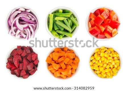 Variety of cut vegetables in white bowls isolated in white
