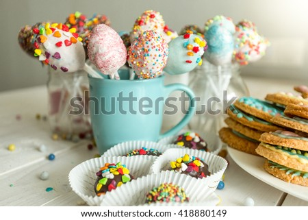 Variety of decorated candies, cake pops and cookies on white wooden desk - stock photo