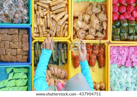 """Variety of delicious and colorful Malaysian home cooked local cakes or """"kueh"""" sold at street market stall in Kota Kinabalu Sabah from top angle view with seller arranging the cake. - stock photo"""