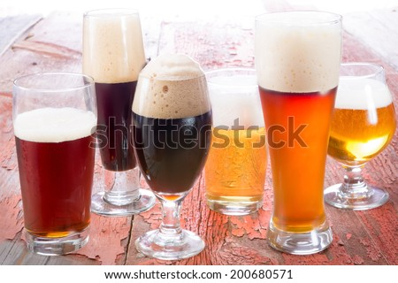 Variety of different beers, of different colors and alcoholic strengths in different shaped glasses suited to different personalities - stock photo