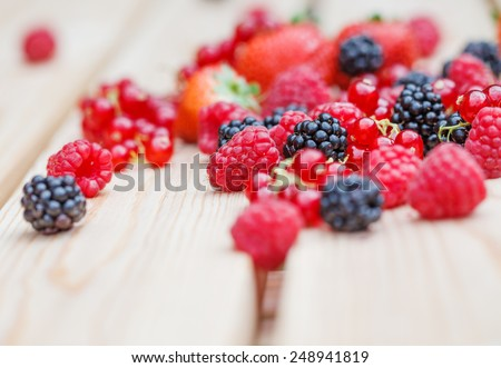 Variety of different berries on a wooden table - stock photo