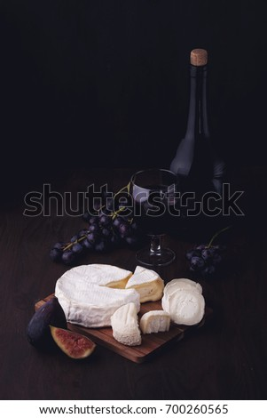 Variety of different cheese with wine and fruits.