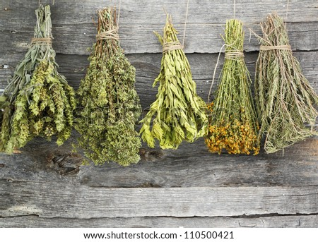 Variety of dried herbs on an old wooden background - stock photo