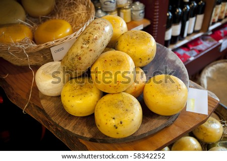 Variety of Dutch cheeses on a board and in a basket - stock photo