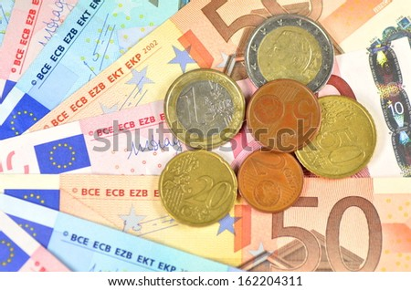 variety of euro banknotes and coins - stock photo
