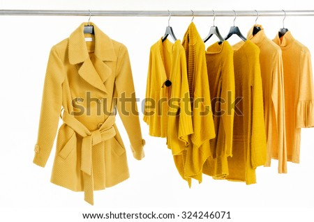 Variety of female yellow clothing on hanging - stock photo
